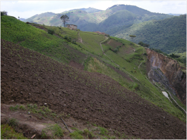 Crop fields cleared on steep slopes above the mine