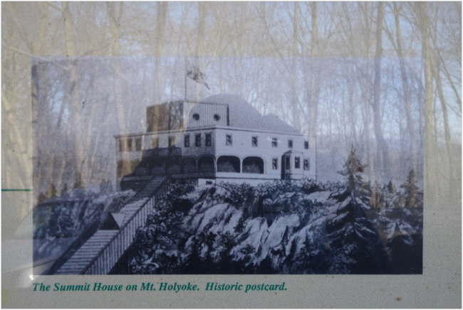 Historic postcard showing the Mt. Holyoke Summit House. Displayed at an informational kiosk, the photo also reflects the forest at the trailhead